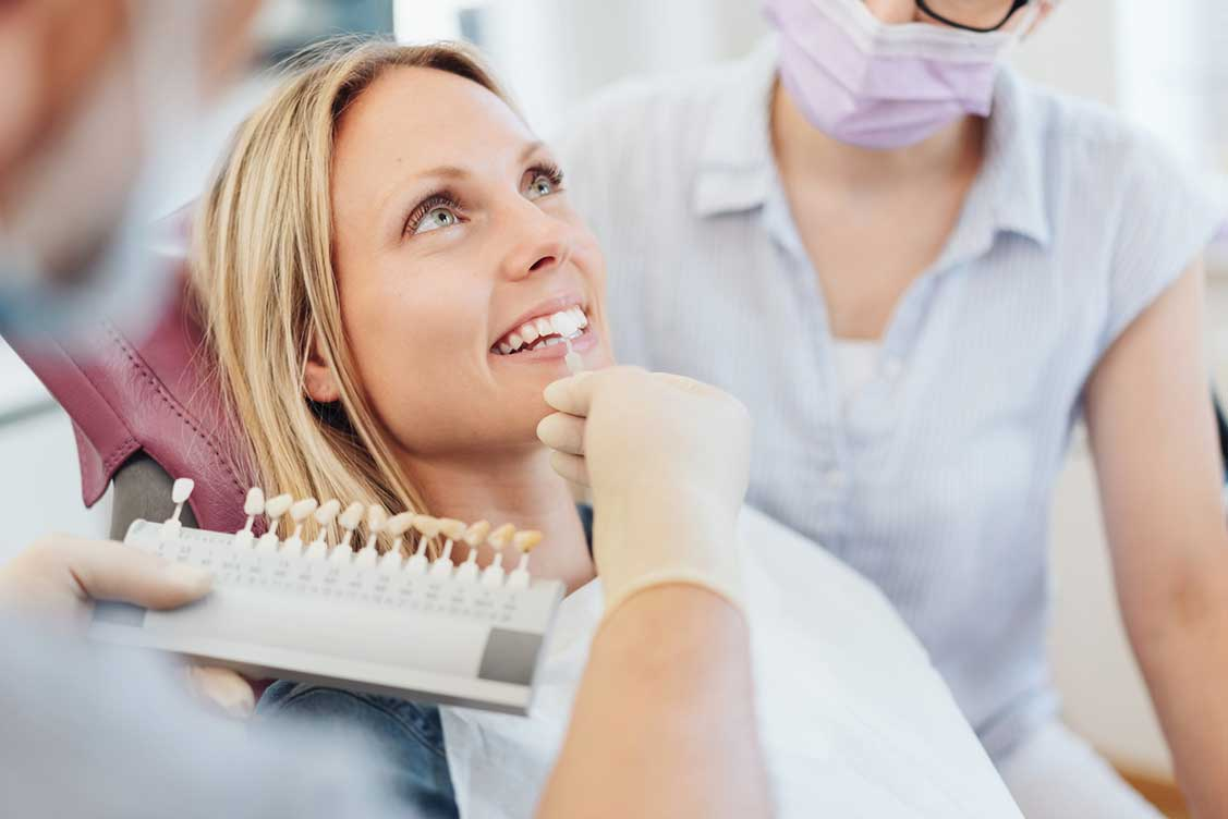 Dentist checking shade chart for woman's veneers